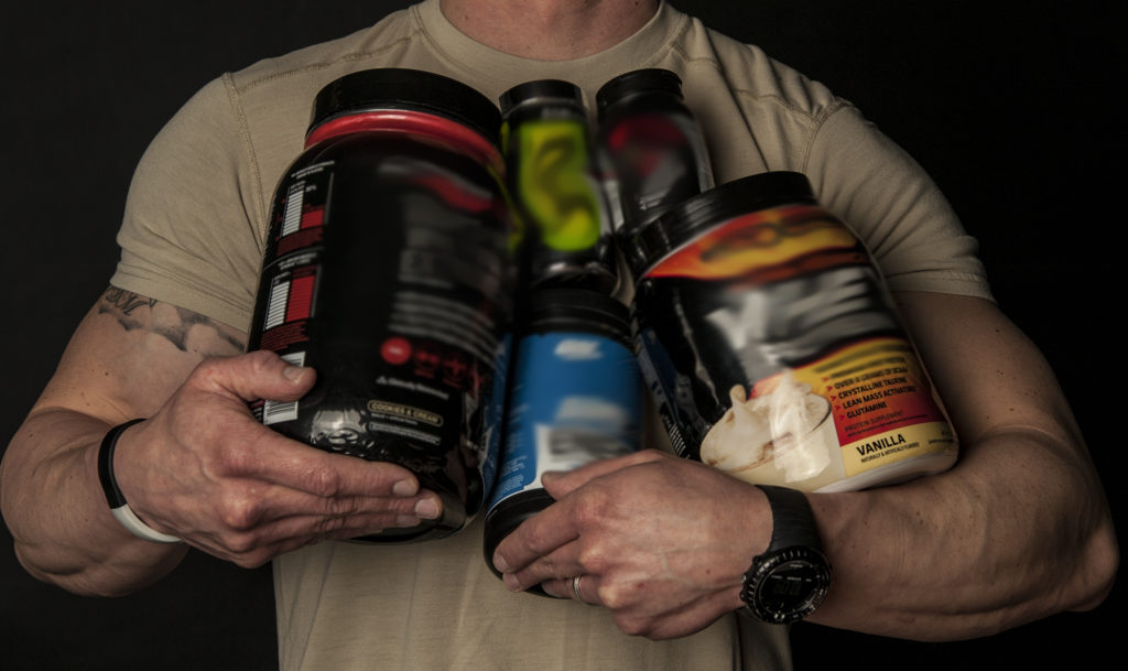 man standing holding supplements