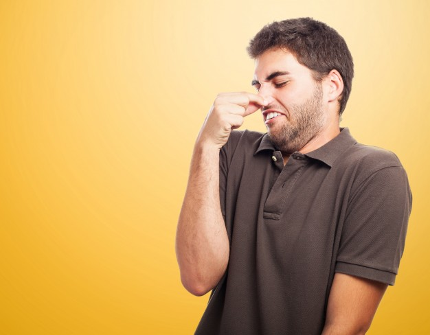 close-up-teen-with-brown-t-shirt-holding-his-nose