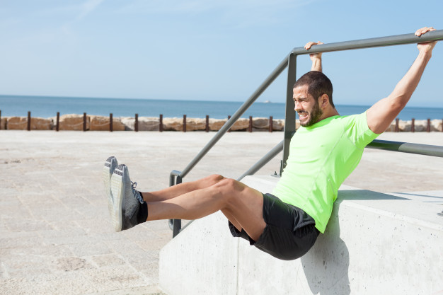 man doing hanging leg raise exercise
