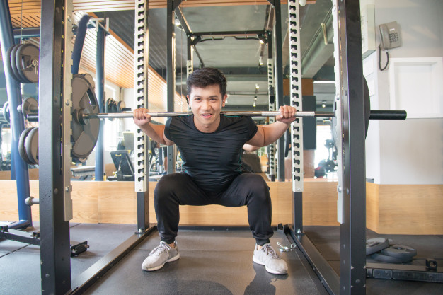 man doing barbell squat exercise