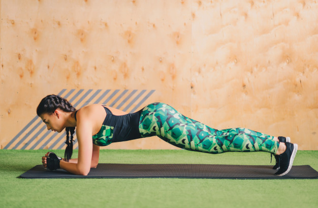 fit woman doing plank indoor yoga mat
