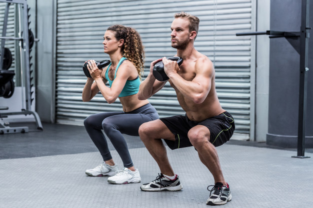 Couple doing dumbbell squats