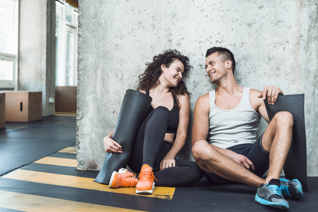 man and woman sitting in the gym