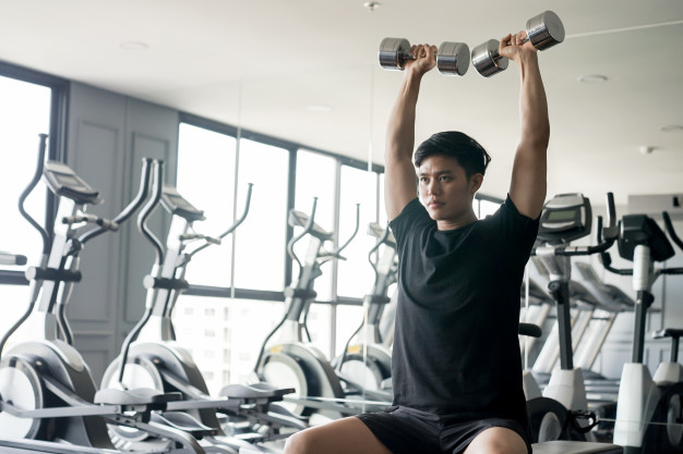 asian-man-holding-dumbbell-raising-playing-shoulder-press-gaining-muscle-gym