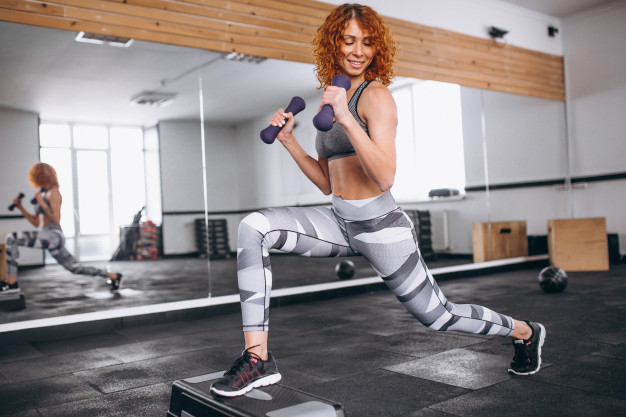 fitness-woman-doing-lunges-with-dumbbells-gym