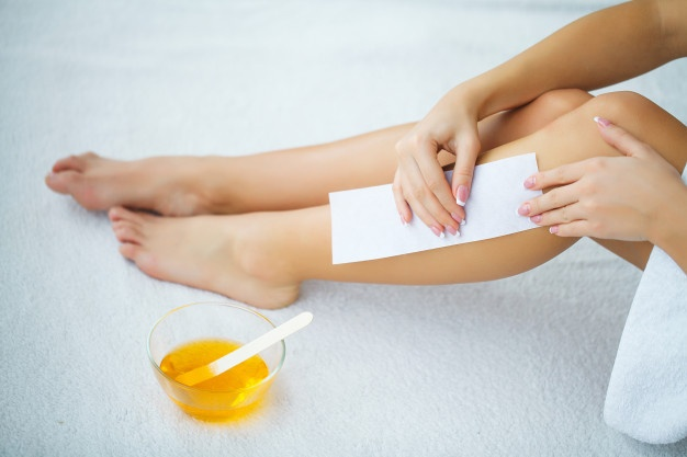 woman waxing leg hairs at home