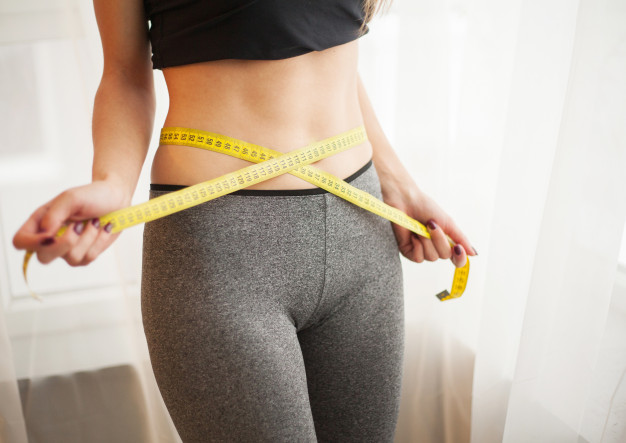 slim-young-woman-measuring-her-thin-waist-with-tape-measure