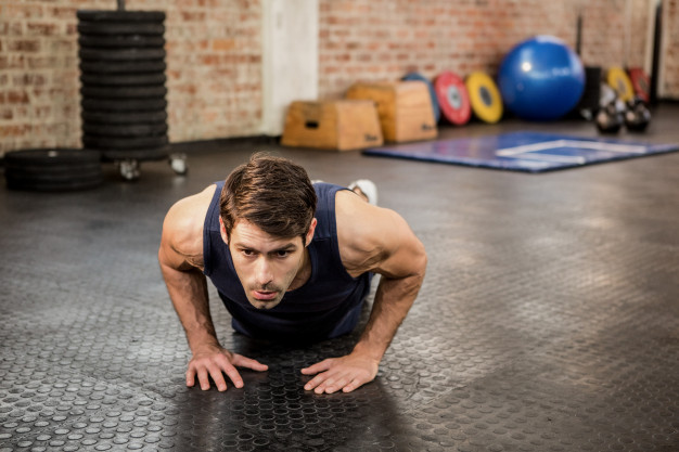 handsome man doing triangle push ups for triceps size
