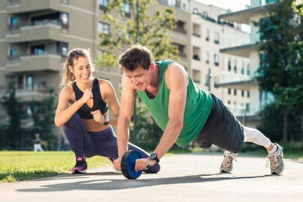 couple doing ab roller abs exercise