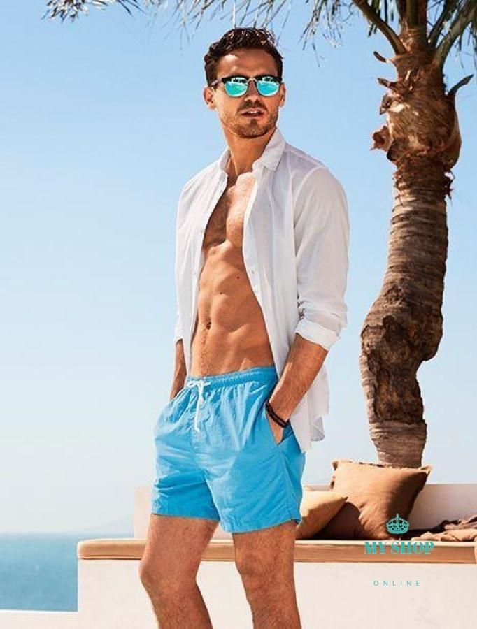 handsome men on the beach wearing broad shorts