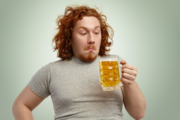 clueless-red-haired-young-man-with-curly-hair-holding-glass-light-beer-looking-it-having-confused-indecisive-expression-hesitating-thinking-drink-it-better-sleep
