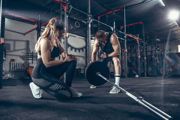fit man and woman weight training gym