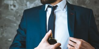 man in handsome suit using cologne winter